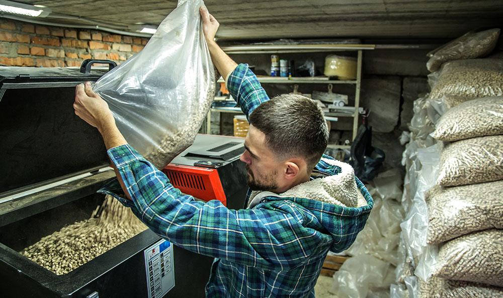 Mężczyzna uzupełniający pellet w zasobniku pieca